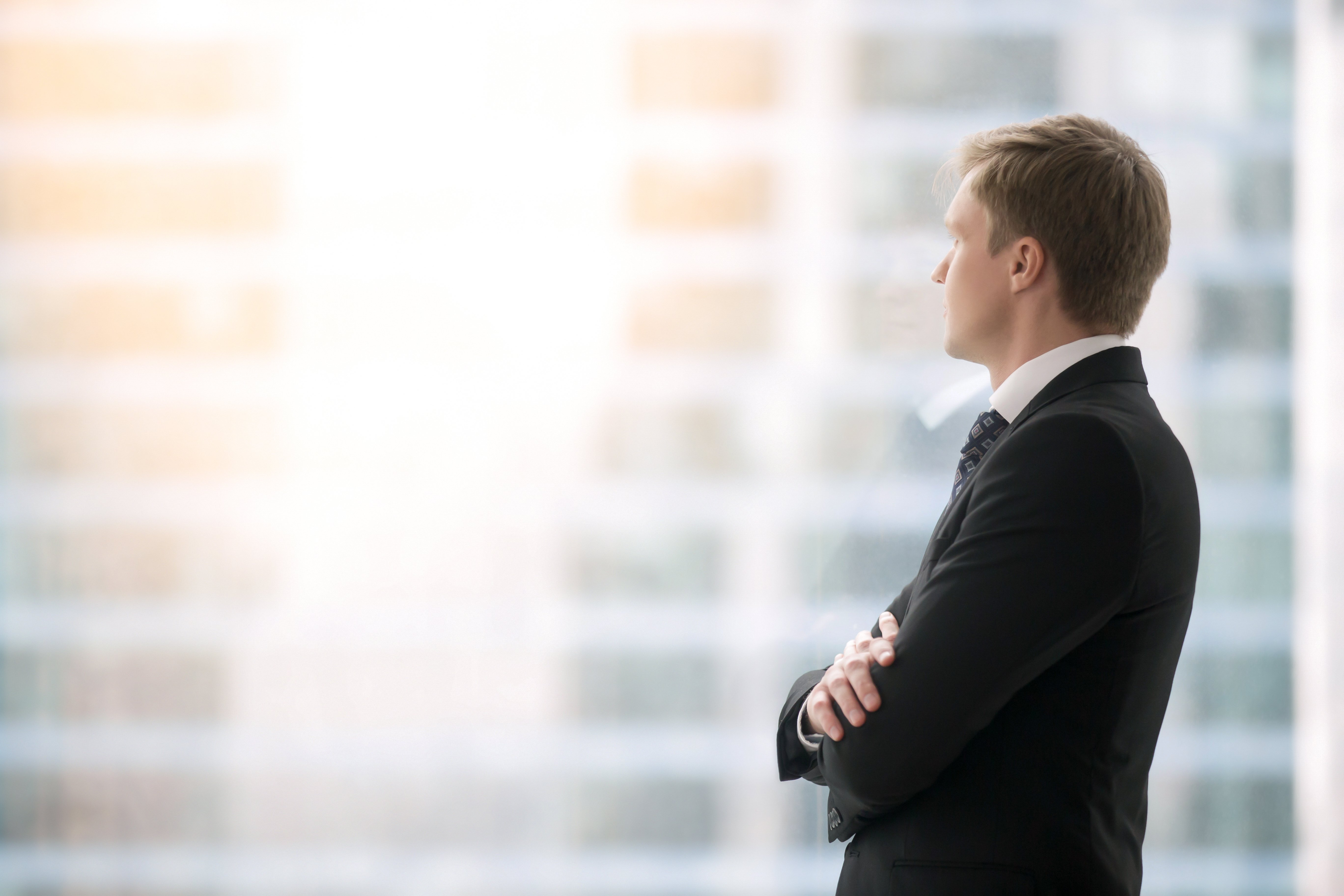 business man waits with arms folded looking ahead