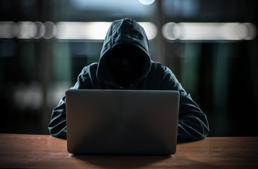 hooded person sat in front of laptop