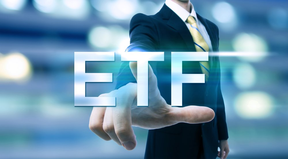 man in suit pointing at ETF writing