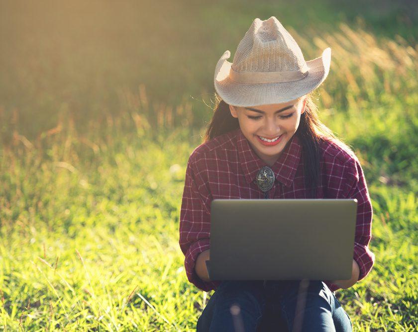 woman using laptop outside in field
