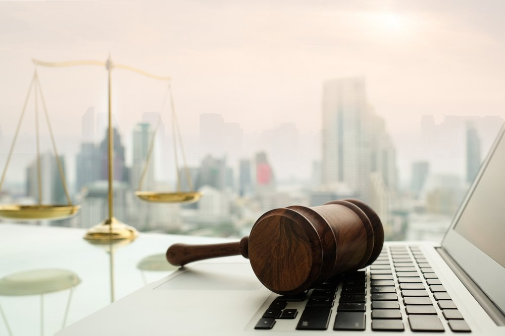 judge gavel on computer with scales of justice on desk