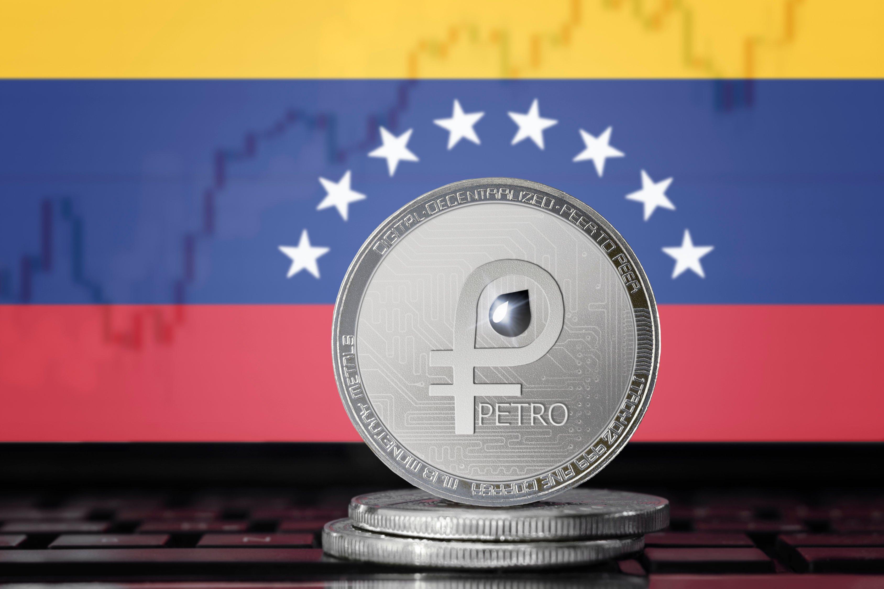 silver petro coin in front of Venezuelan flag