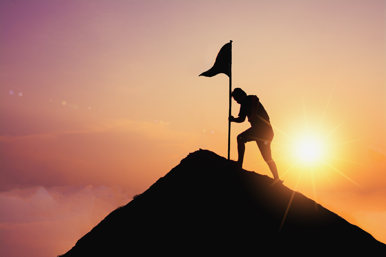 man planting flag up mountain