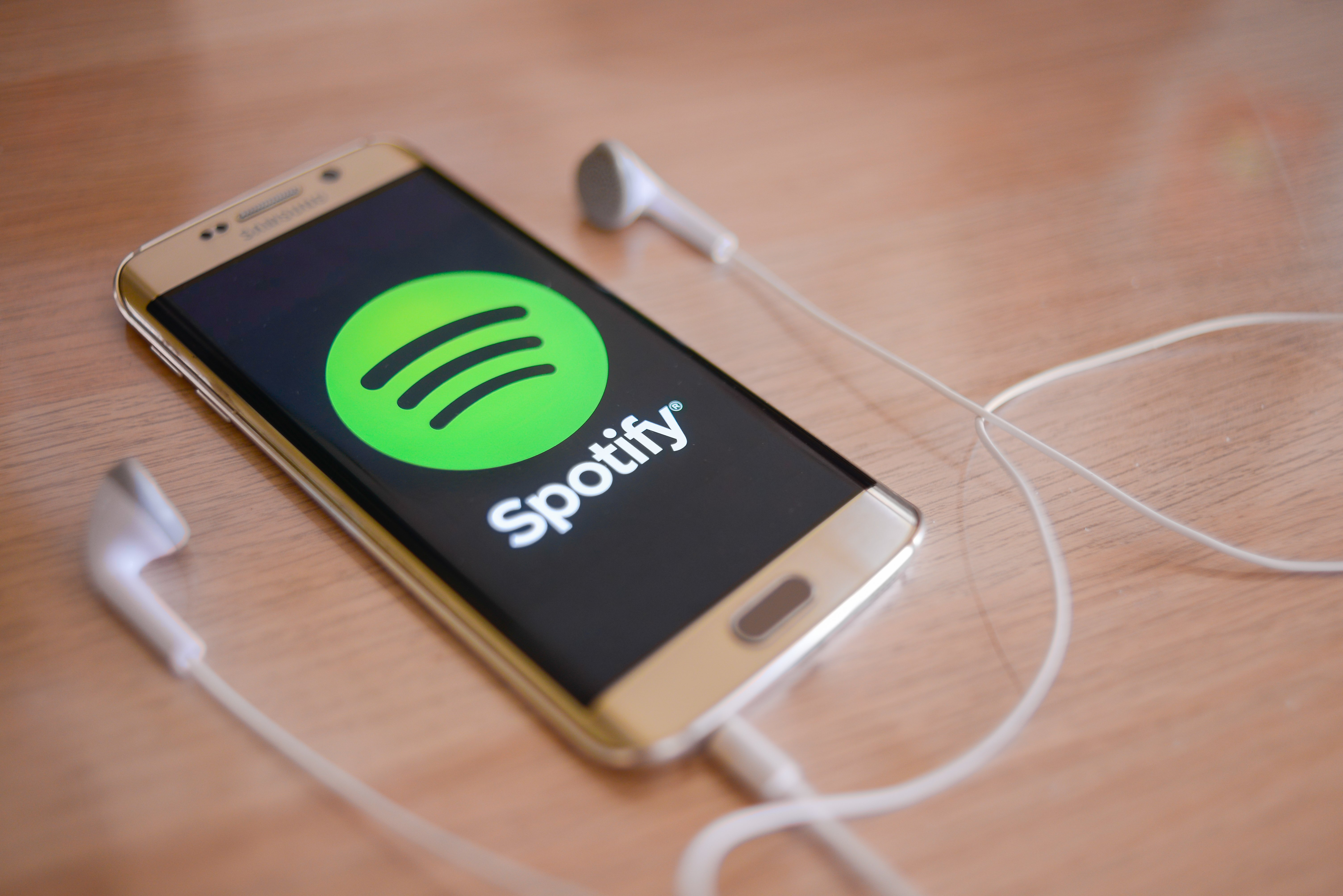 smartphone opening spotify app on wooden table
