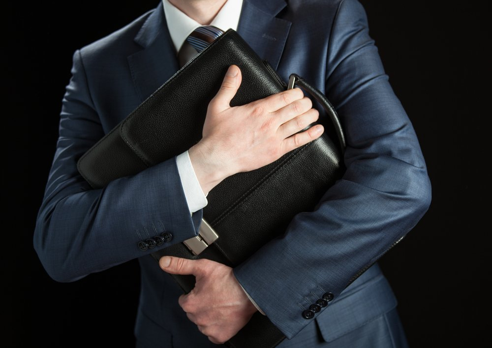 Businessman clasping briefcase to his chest