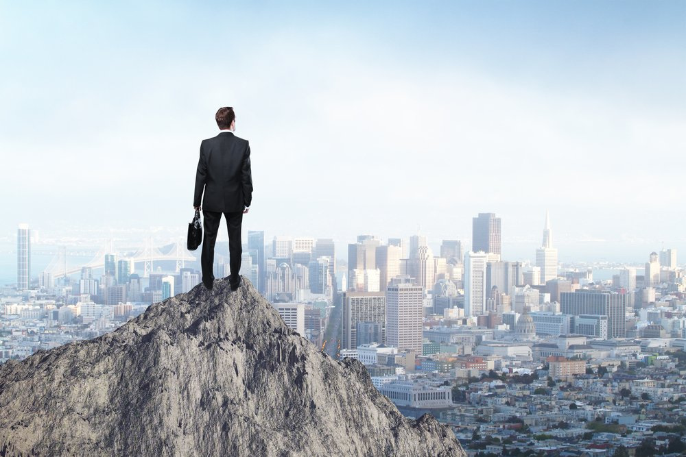 businessman standing on mountain top and looking at city