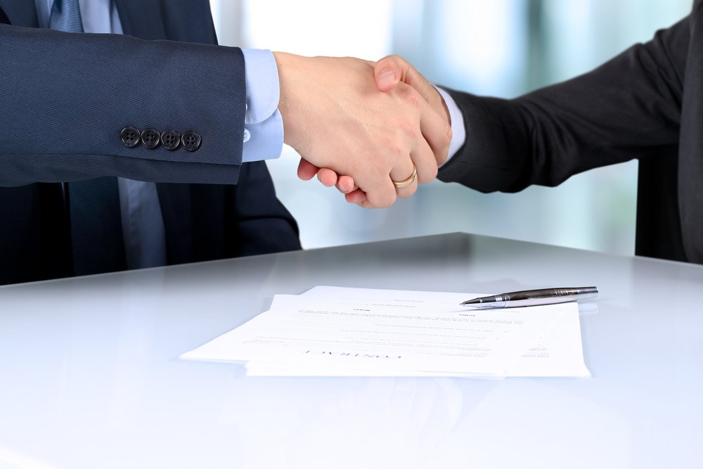 firm handshake between two colleagues after signing a contract