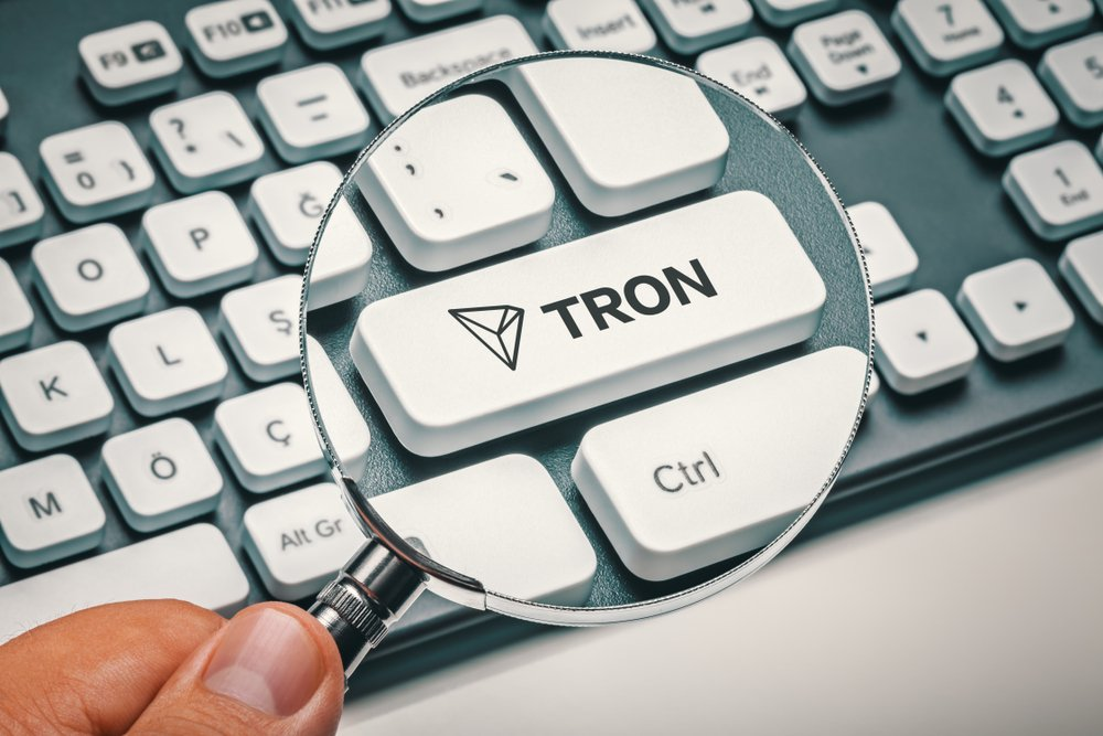 magnifying glass in hand focused on computer key with tron coin logo
