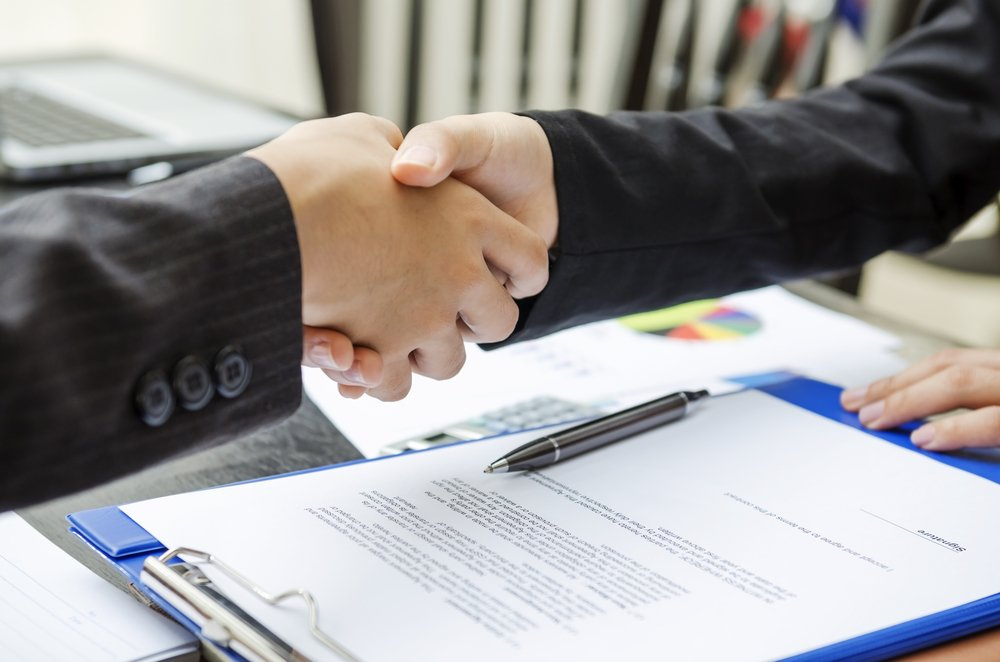 Business person shaking hands as a deal done