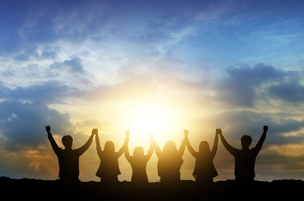 Silhouette of happy business teamwork making high hands over head in sunset sky