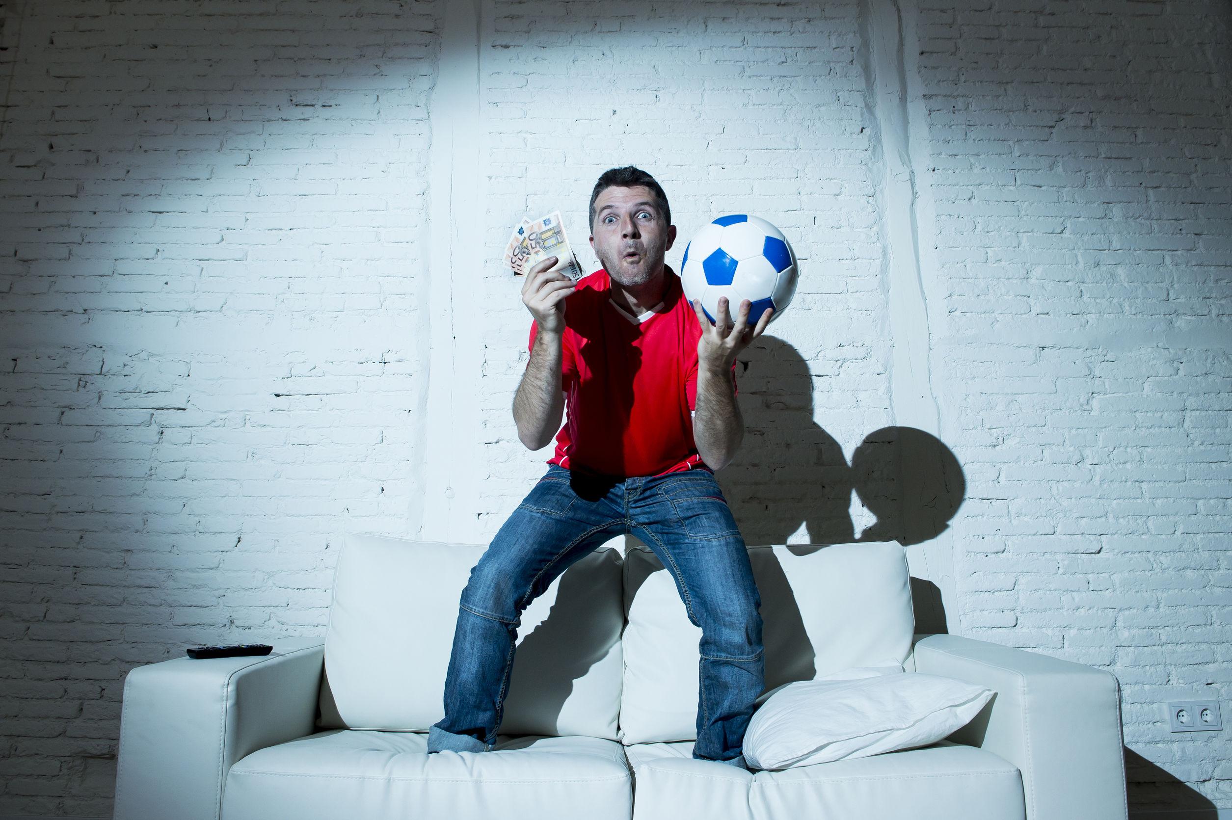 crazy man holding money and soccer ball watching football on tv internet online bet gambling